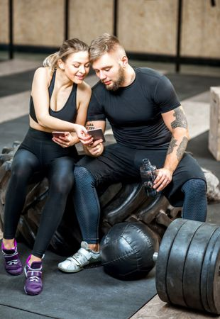 couple checking the trainerize app while working out