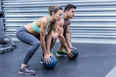 young fit couple training with medicine balls