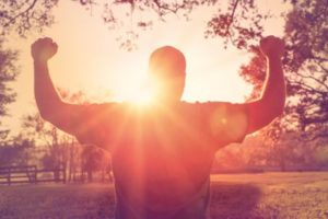 man raising arms in victory against rising sun