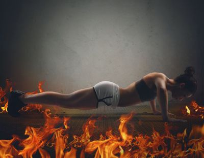Athletic girl is training doing push up surrounded by flames