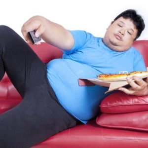overweight man on couch eating pizza and watching tv