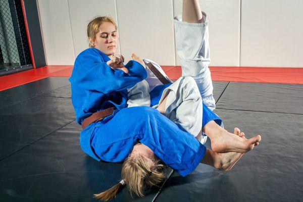A young woman in a kimono makes a painful reception. Judo, jujitsu. Tatami, gym